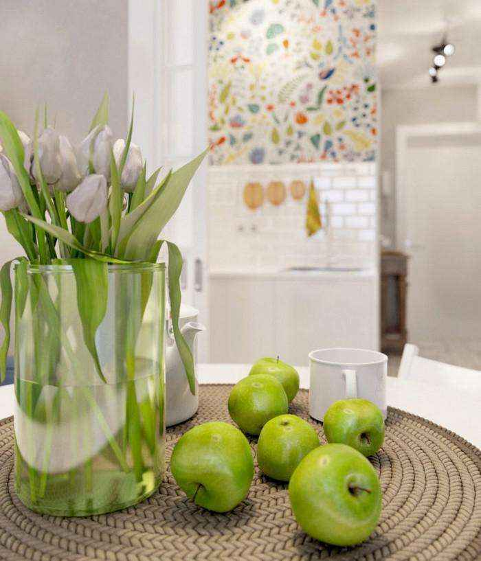 3-2-light-grayish-blue-apartment-interior-decor-in-modern-style-round-dining-table-wicker-napkin-green-apples-flower-vase-tulips-floral-wall-tiles